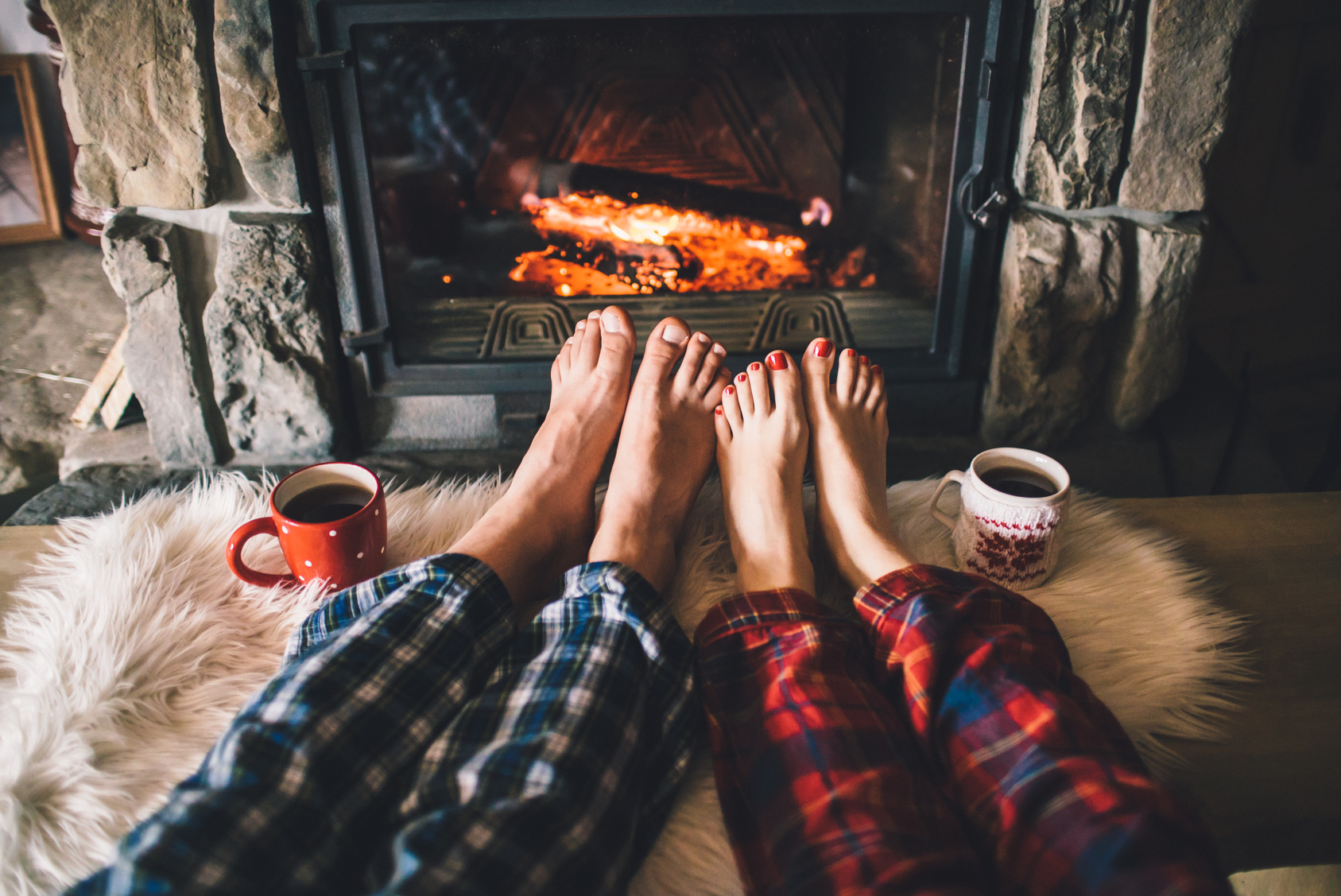 Bare couple feet by the cozy fireplace. Man and Woman relaxes by warm fire with a cup of hot drink and warming up her feet. Close up on feet. Winter and Christmas holidays concept.