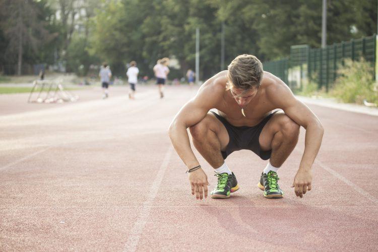 Tired sprinter at start position kneeling.