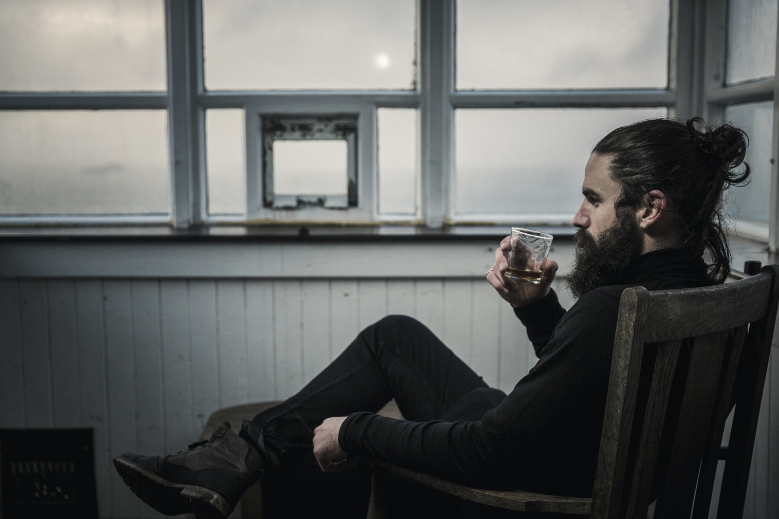 A man sitting looking at the view out of a window, drinking from a glass.