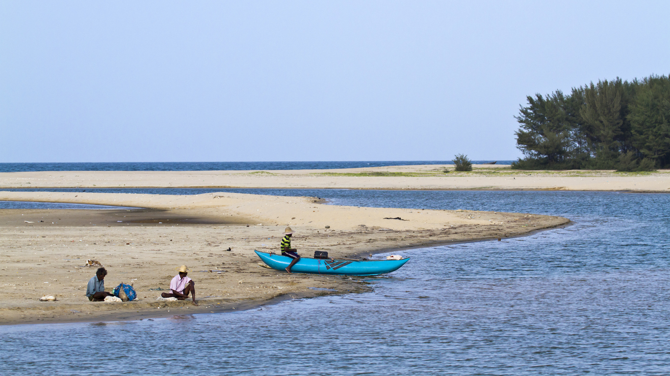 Batticaloa, Sri Lanka - June 25, 2014: Traditional fisherman in Palameenmadu beach, Sri Lanka. They are resting after fishing sitting in sand.