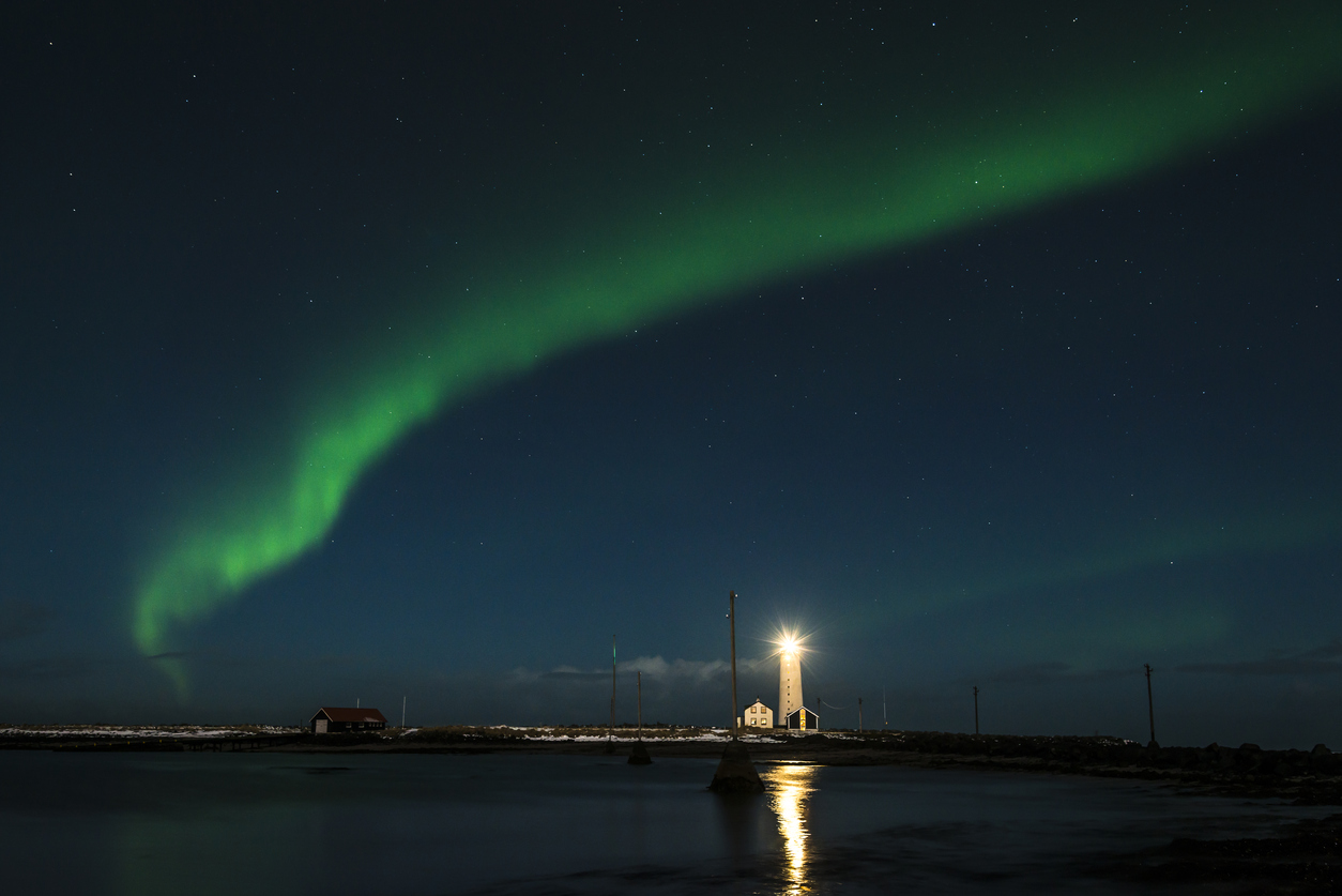 The bright green Aurora Borealis over the lighthouse in Reykjavik. Iceland.