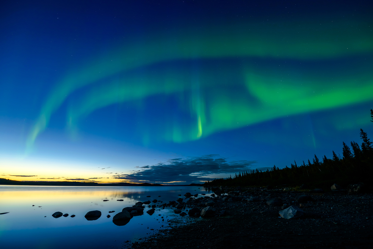 Bands of Northern Lights appear above a rocky lake right after the sun sets.