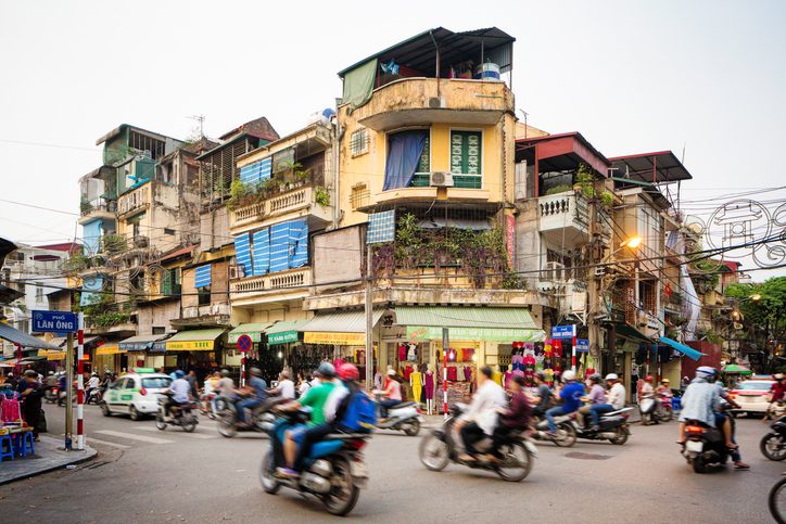 Busy street corner in old town Hanoi, Vietnam. Lots of people are commuting on motorbikes or cars. The street is lined by stores and appartment buildings.