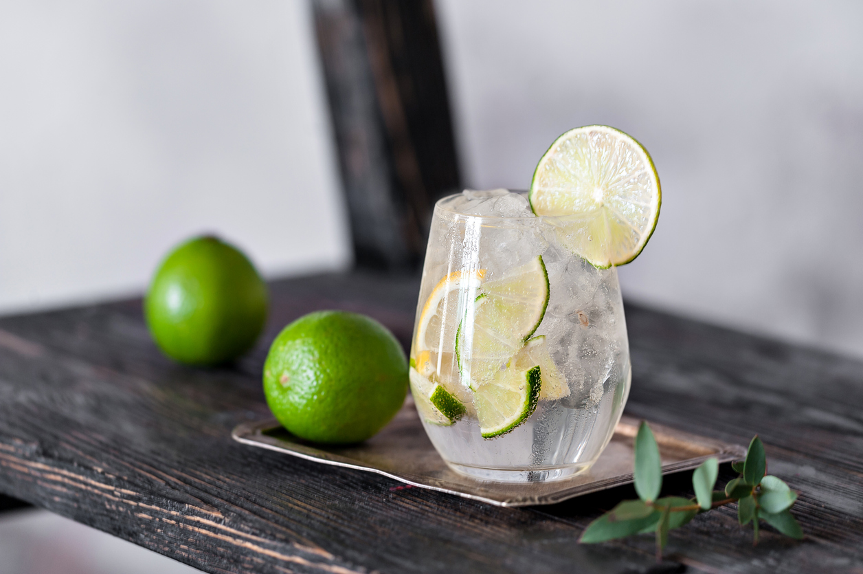 Cold cocktail with lime, lemon, tonic, vodka and ice on vintage background